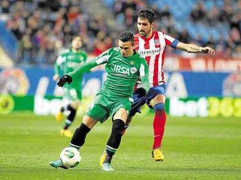 Rubén Castro intenta llevarse el balón ante el atlético Raúl García.