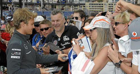 Nico Rosberg firma autógrafos a varios aficionados en Mónaco.