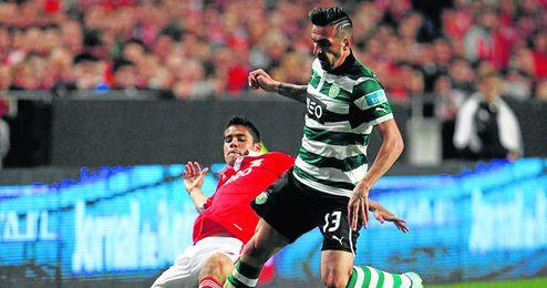 El lateral zurdo del Benfica Lorenzo Melgarejo trata de frenar el avance de Miguel Lopes en un partido de la 12/13.