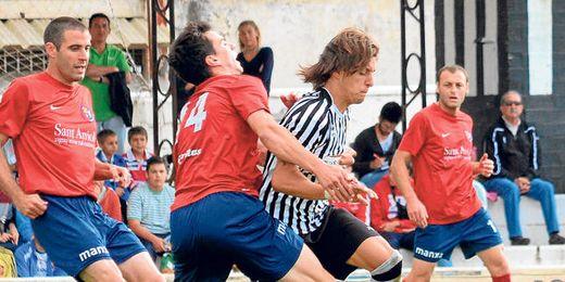 El centrocampista blanquinegro Paquito trata de zafarse de la presión de varios rivales olotenses en los ´play off´.
