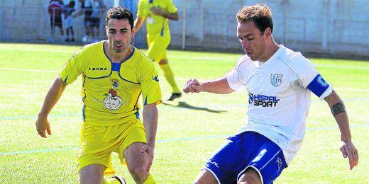 En la imagen, el capitán del conjunto alcalareño despeja la pelota ante la presión de un futbolista del San Juan.