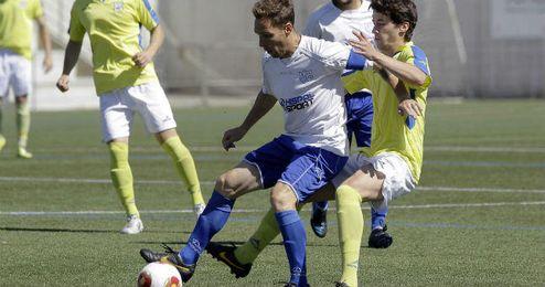 Gonzalo, capitán panadero y autor del primer gol, protege el balón ante la presión del coriano Álvaro Vélez.