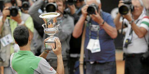 Djokovic posa con el trofeo antes de donarlo por las catástrofes de su país