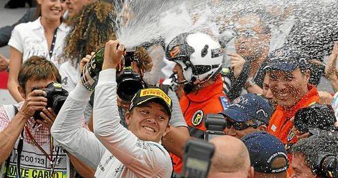 Rosberg celebra el triunfo en Mónaco bañando en champán a sus compañeros.