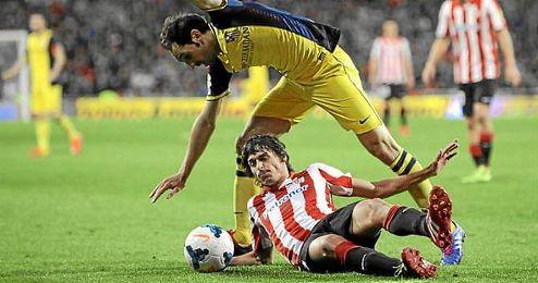 Ander Iturraspe del Athletico de Bilbao lucha contra Juanfran del Atletico de Madrid en el estadio San Mames.