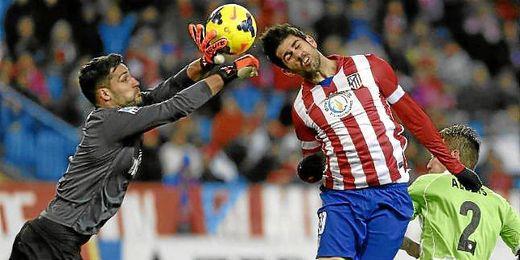 Moyá salta junto a Diego Costa en un balón dividido.