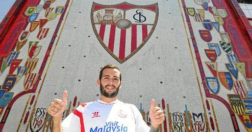Aleix Vidal posa con su nueva camiseta junto al mosaico del estadio.