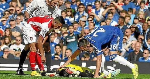 Terry y Alexis atienden a Courtois tras chocar con el chileno del Arsenal.