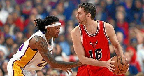 Gasol protege el balón ante un jugador de los Lakers.