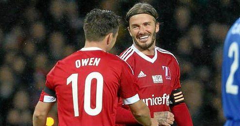 Beckham dialoga con Owen sobre el césped.