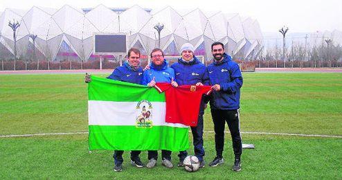 Los cuatro t�cnicos sevillanos posan con la bandera de Andaluc�a y la camiseta de la selecci�n de China.