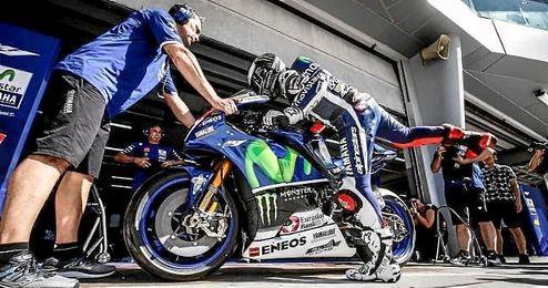 Jorge Lorenzo subiéndose a su moto en el box de Yamaha en Sepang.