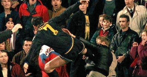 Eric Cantona, en el momento de propinarle una patada a un aficionado