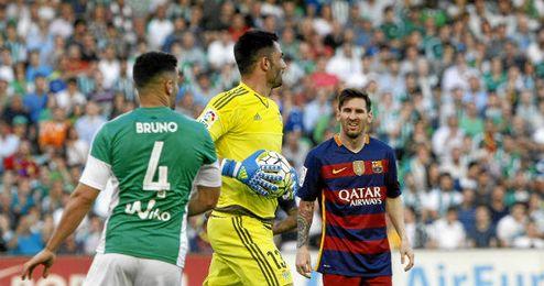 Adán atrapa el balón ante Bruno y messi.