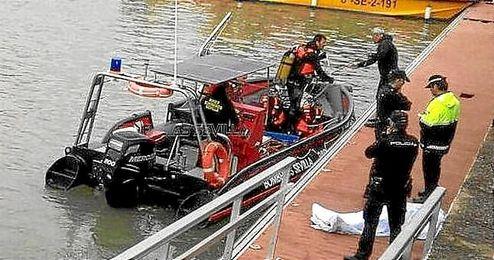 Imagen del rescate del cuerpo sin vida en el Guadalquivir.