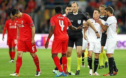 Jonas Eriksson lidiando entre los jugadores de Sevilla y Liverpool.