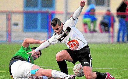 Javi Muñoz se tira al suelo para cortar el avance de un rival en un Brenes-Coronil de la 12/13.