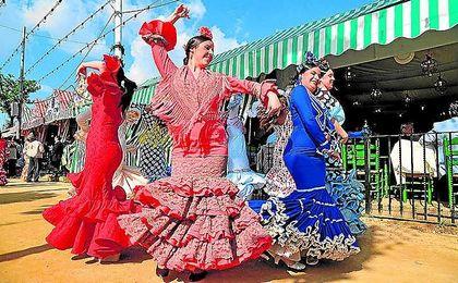 Varias transe�ntes bailan la tradicional �sevillana� en las calles del recinto ferial.