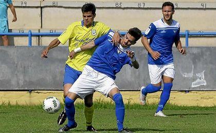 El azulino Juanito, que abrió el marcador con un golazo, es sujetado por el capitán coriano Israel.