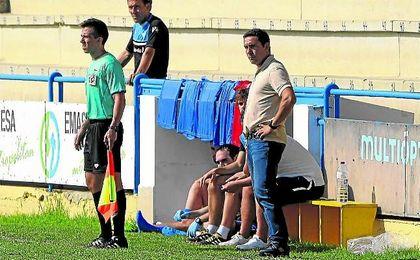 Juan Carlos Gómez, entrenador del Écija, pendiente de sus jugadores en un lance del Coria-Écija.