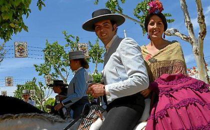 Imagen de una pareja por el Real de la Feria de Abril.