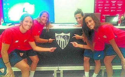 Pamela y Alicia por la izquierda, y Maite y Nagore por la derecha, posan para ESTADIO señalando el escudo del Sevilla Fútbol Club.