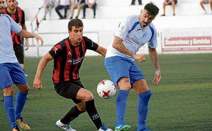 Javi Salas y Serrano disputan un balón en el partido del domingo.