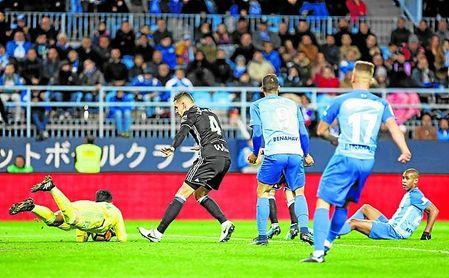 Feddal frena con el cuerpo a los delanteros del Málaga mientras que Adán atrapa la pelota.