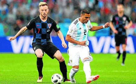 Mercado despeja el balón ante la presión del exsevillista Ivan Rakitic.
