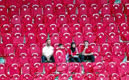 Aficionados en un estadio rodeados por banderas de Turquía.